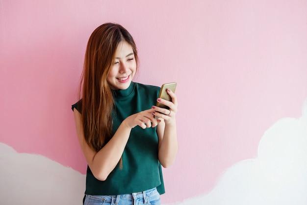 Portret van een jonge vrouw lachend tijdens het gebruik van de slimme telefoon aan de muur