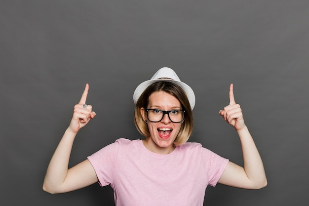 Portret van een jonge vrouw lachende wijzende vingers omhoog tegen grijze muur