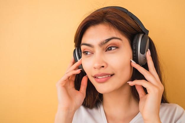 Portret van een jonge vrouw, luisteren naar muziek met een koptelefoon