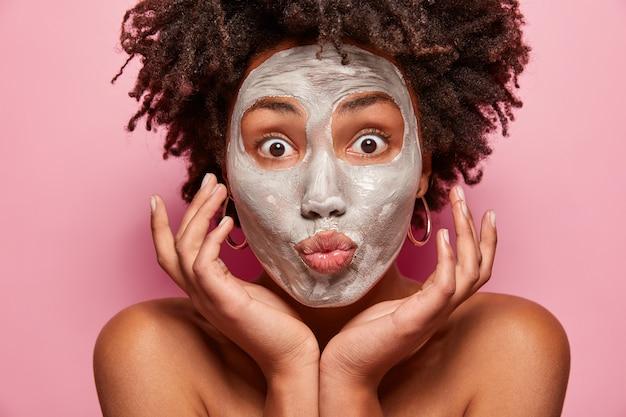 Portret van een jonge vrouw met afro-kapsel en gezichtsmasker