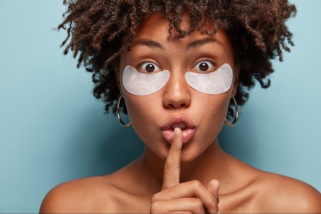 Portret van een jonge vrouw met afro-kapsel en ooglapjes