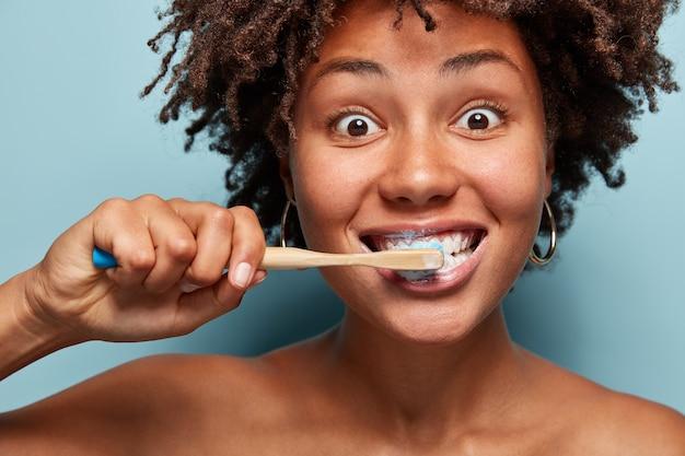 Portret van een jonge vrouw met afro kapsel haar tanden poetsen