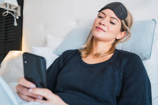 Portret van een jonge vrouw met behulp van haar mobiele telefoon terwijl het leggen op bed in hotelkamer. reis- en levensstijlconcept.