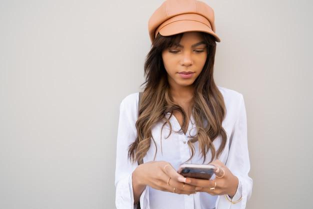 Portret van een jonge vrouw met behulp van haar mobiele telefoon terwijl ze buiten op straat staat.