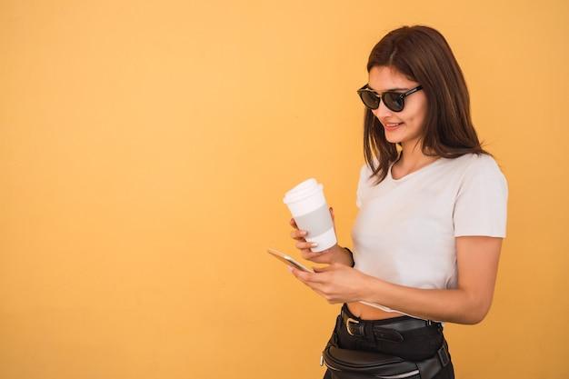 Portret van een jonge vrouw met behulp van haar mobiele telefoon terwijl ze een kopje koffie buiten op straat houdt