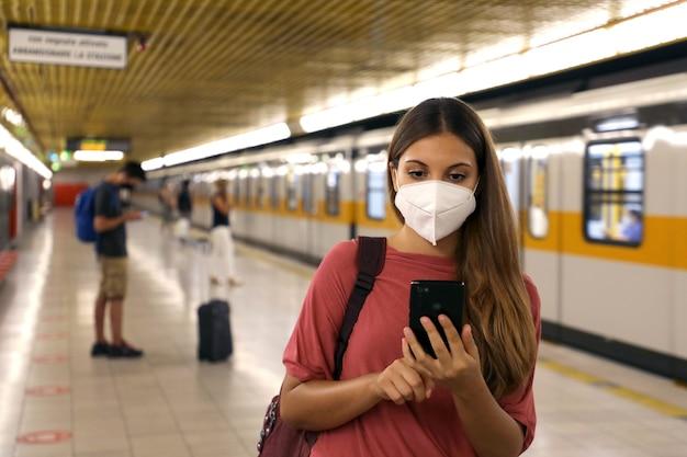 Portret van een jonge vrouw met beschermend masker met behulp van slimme telefoon-app in het metrostation