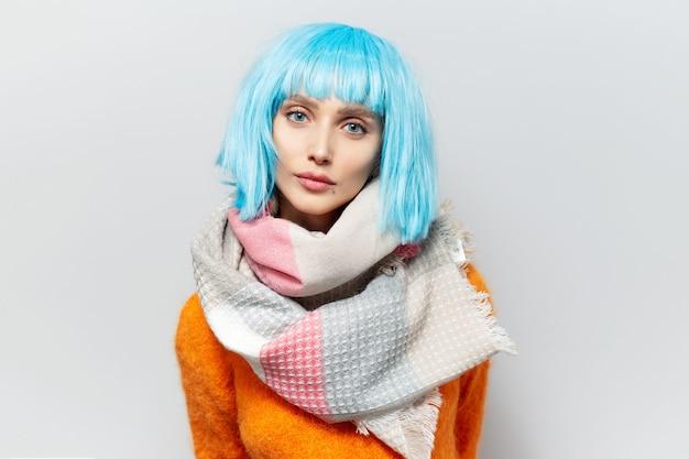 Portret van een jonge vrouw met blauw kapsel in oranje trui, sjaal dragen. op witte muur.