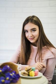 Portret van een jonge vrouw met bloemboeket en bitterkoekjes op plaat