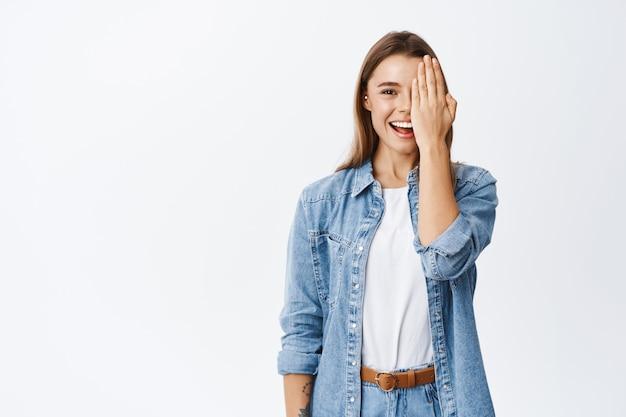 Portret van een jonge vrouw met blond haar, bedek de helft van het gezicht met make-up met natuurlijk licht, laat zien voor het effect of controleer het zicht in de opticienwinkel, witte muur