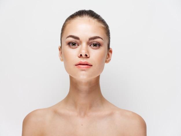Portret van een jonge vrouw met blote schouders, heldere huid kapsel jeugd