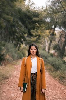 Portret van een jonge vrouw met boek in de hand staande op bospad
