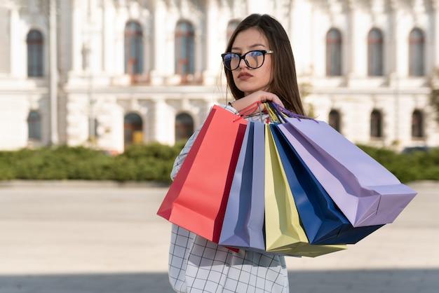 Portret van een jonge vrouw met boodschappentassen achter haar rug. succesvol winkelen.