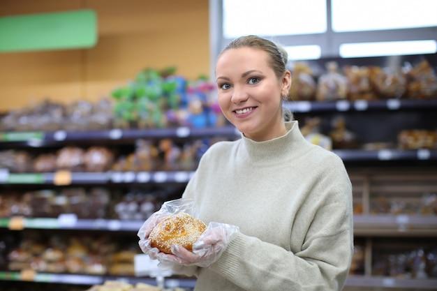 Portret van een jonge vrouw met broodje in winkel. eigenaar van een klein bedrijf