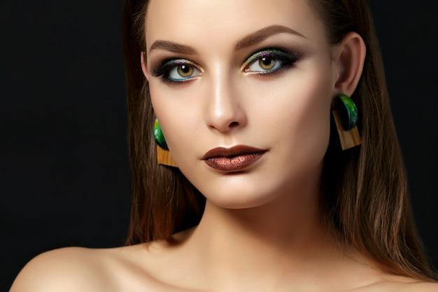 Portret van een jonge vrouw met bruine lippen en groene smokey eyes close-up. perfecte wenkbrauwen. moderne mode-make-up.