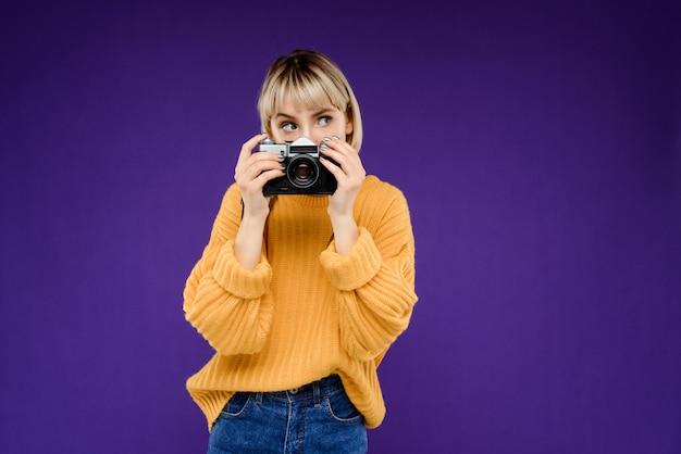 Portret van een jonge vrouw met camera over paarse muur