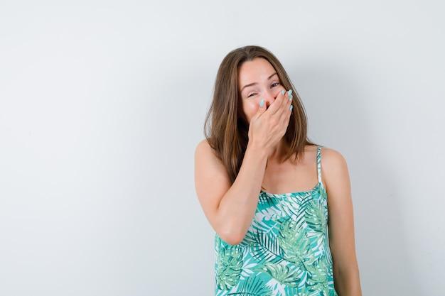Portret van een jonge vrouw met de hand op de mond en op zoek naar een gelukkig vooraanzicht