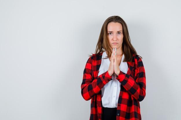 Portret van een jonge vrouw met de handen in een biddend gebaar in vrijetijdskleding en een droevig vooraanzicht