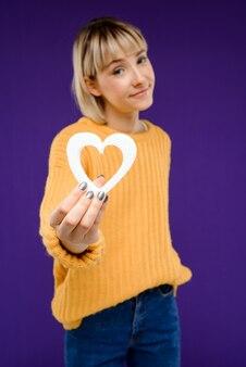Portret van een jonge vrouw met decor hart over paarse muur