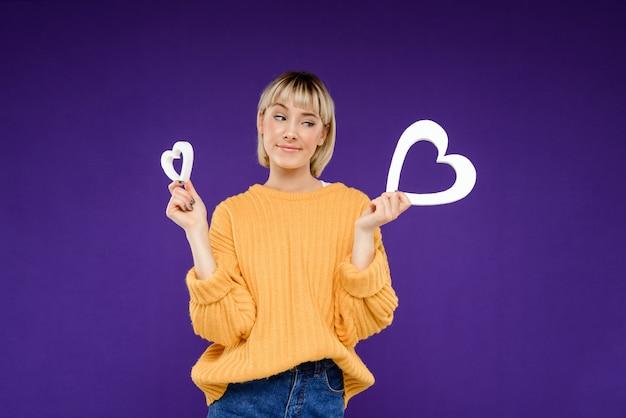 Portret van een jonge vrouw met decor harten over paarse muur