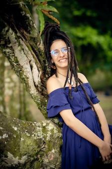 Portret van een jonge vrouw met dreadlocks die op een boom liggen en bij de camera glimlachen.