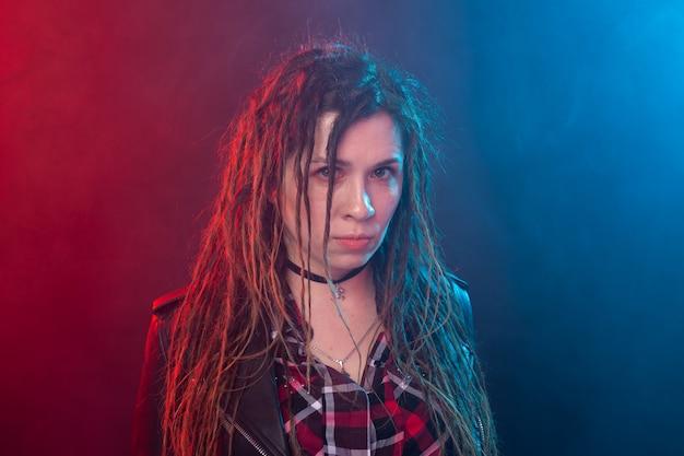 Portret van een jonge vrouw met dreadlocks die pret over de donkere muur hebben