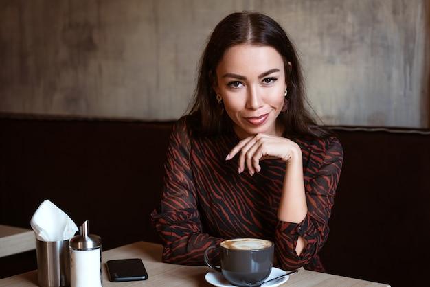 Portret van een jonge vrouw met een blanke uitstraling in een café met een kopje koffie mooie brunette ...
