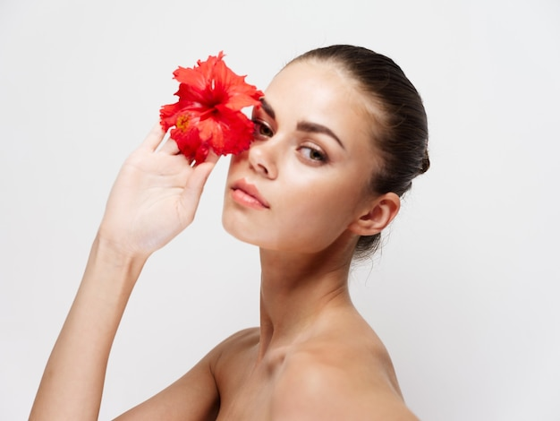Portret van een jonge vrouw met een bloem in haar hand op een lichte achtergrond, schone huidkosmetiek