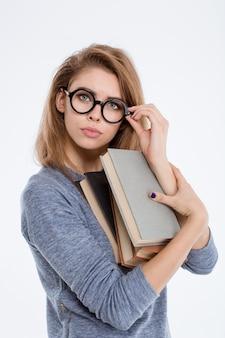 Portret van een jonge vrouw met een bril die boeken vasthoudt en naar een camera kijkt die op een witte achtergrond wordt geïsoleerd