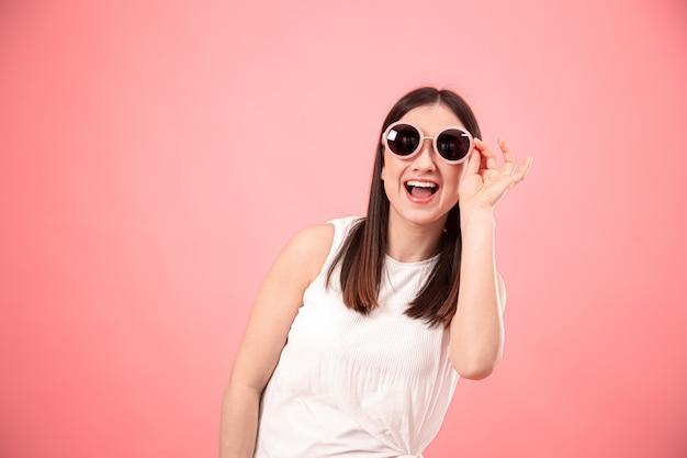 Portret van een jonge vrouw met een bril op een roze achtergrond.