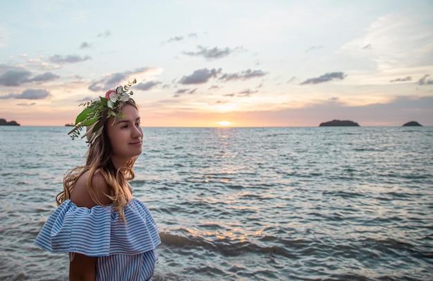 Portret van een jonge vrouw met een compositie van bloemen op haar hoofd tegen de achtergrond van de oceaan bij zonsondergang.