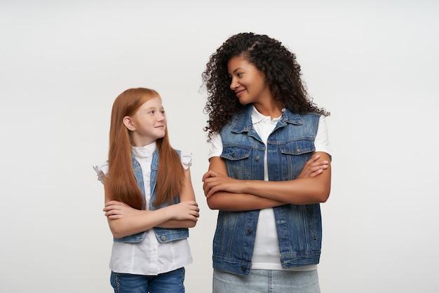 Portret van een jonge vrouw met een donkere huid en een foxy langharig meisje die hun handen gevouwen op de borst houden en naar elkaar kijken met een positieve glimlach, geïsoleerd op wit