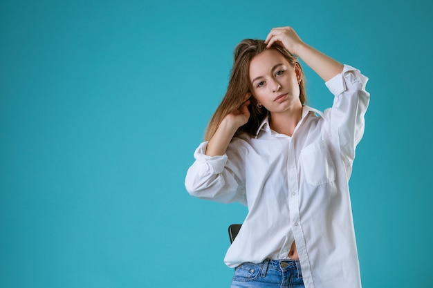 Portret van een jonge vrouw met een droevig gezicht in een wit overhemd op een blauwe muur