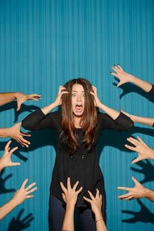 Portret van een jonge vrouw met een geschokte gezichtsuitdrukking en de handen van veel mensen