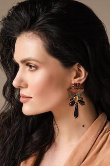 Portret van een jonge vrouw met een gezonde huid en oorbellen op haar oren geïsoleerd op de muur