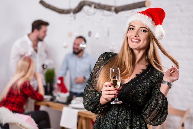 Portret van een jonge vrouw met een glas champagne thuis op de voorgrond mooie blonde in een ...