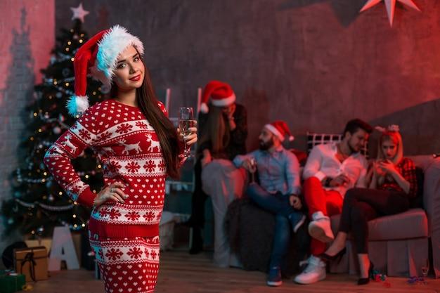 Portret van een jonge vrouw met een glas champagne thuis op de voorgrond. mooie brunette in een kerstmuts, rood kostuum met herten