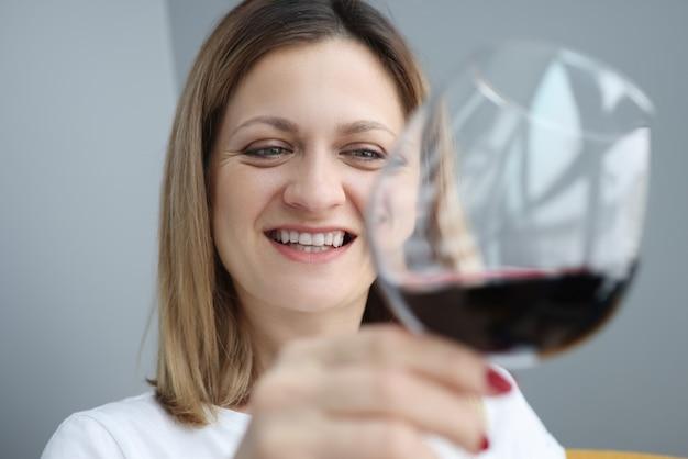 Portret van een jonge vrouw met een glas rode wijn in haar hand