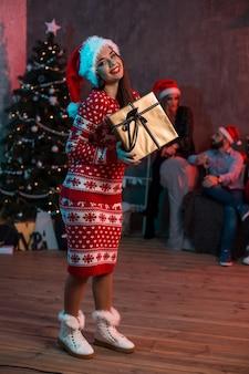 Portret van een jonge vrouw met een gouden geschenkdoos thuis op de voorgrond. mooie brunette in een kerstmuts, rood kostuum met herten
