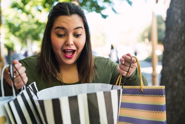 Portret van een jonge vrouw met een grote maat die boodschappentassen vasthoudt en er opgewonden uitziet buitenshuis op straat