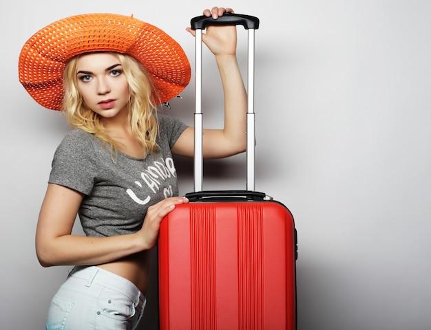Portret van een jonge vrouw met een grote strooranje hoed die staat met een oranje reistas