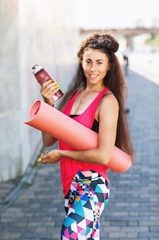 Portret van een jonge vrouw met een gymnastiekmat en een fles water in haar handen op straat