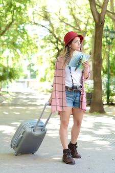 Portret van een jonge vrouw met een kaart en op zoek naar een routebeschrijving terwijl ze koffer buiten op straat draagt. reis concept.