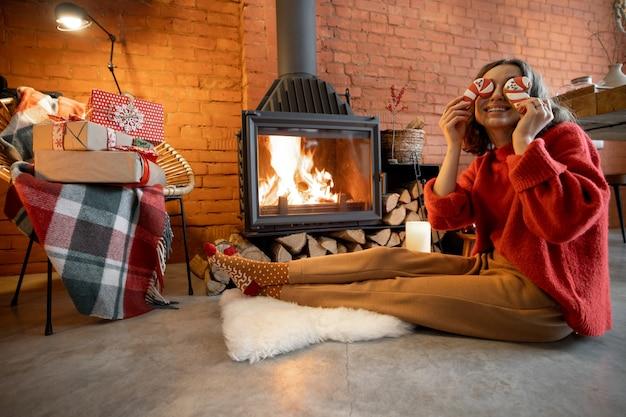 Portret van een jonge vrouw met een kerstsnoep bij de open haard. huis gezelligheid en warmte tijdens de wintervakantie