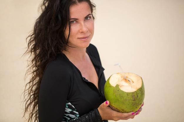 Portret van een jonge vrouw met een kokosnoot in haar handen op het strand.
