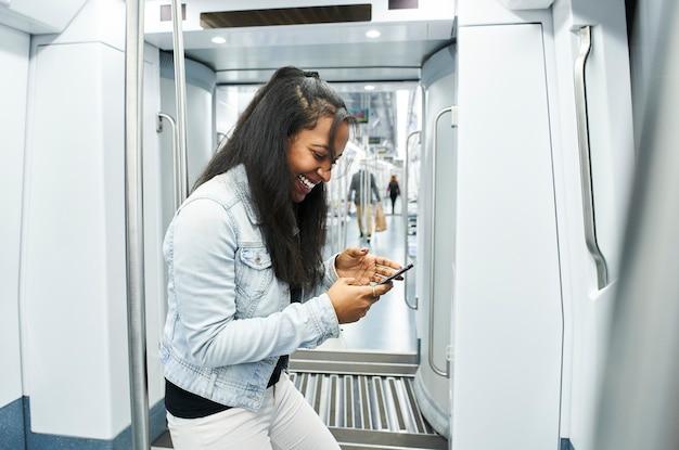 Portret van een jonge vrouw met een masker die haar celtelefoon in de metroauto gebruikt.