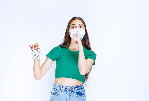 Portret van een jonge vrouw met een medisch masker die een wekker houdt.