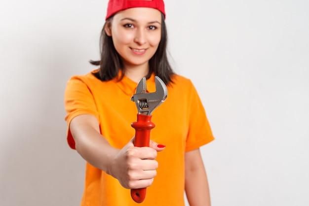 Portret van een jonge vrouw met een moersleutel in haar hand. op wit
