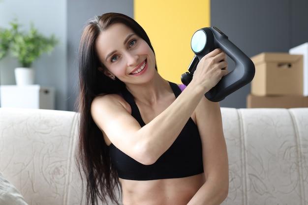 Portret van een jonge vrouw met een percussiemassageapparaat in haar handen thuis