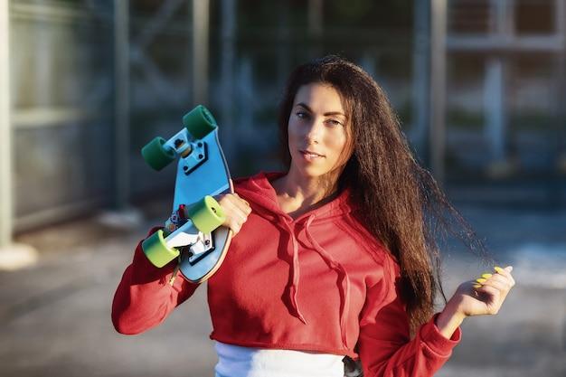 Portret van een jonge vrouw met een skateboard in haar handen op een zonnige zomeravond