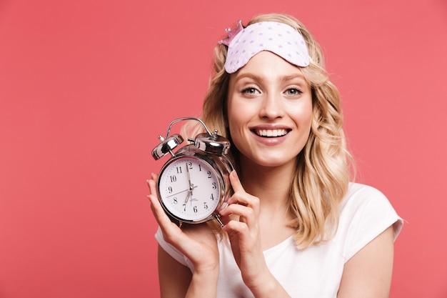 Portret van een jonge vrouw met een slaapmasker met een wekker na het ontwaken, geïsoleerd over een rode muur